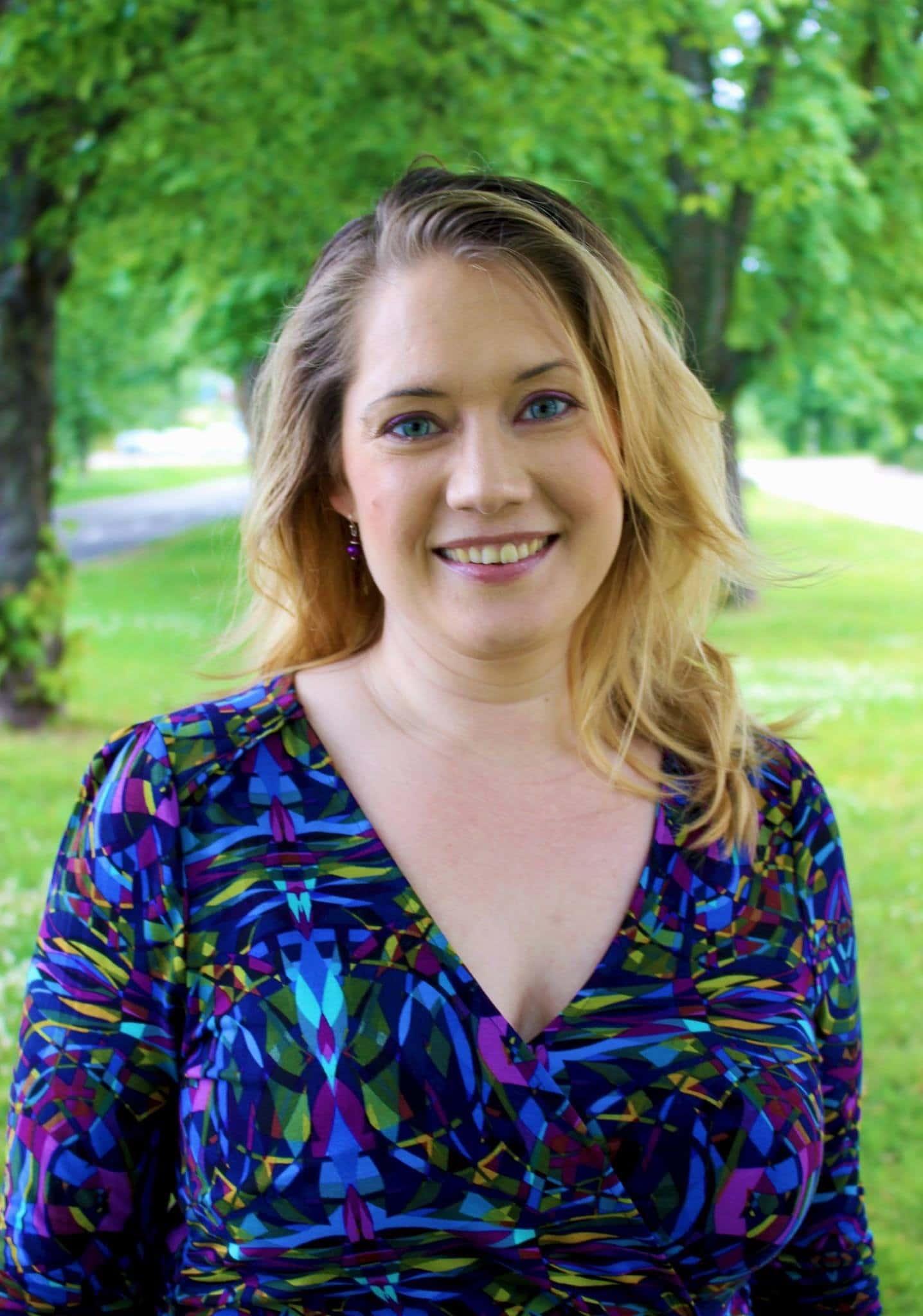 Carola Bolmstedt porträttbild. Hon är klädd i blått på överdelen en sommardag i en park.