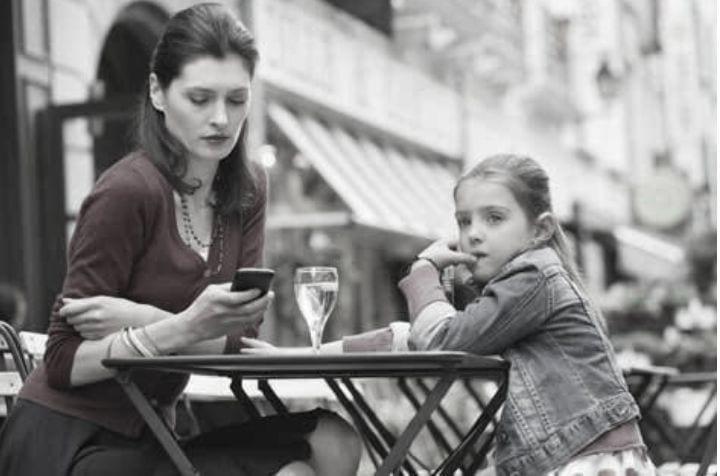 Mor och dotter sitter på uteservering, fotot är svartvitt