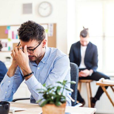 Frustrerad person vid skrivbord